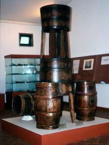 """Macchina per filtrare il mosto per la produzione di """"vin dolce""""; in basso, barili da vino, Montescudaio, 1940 circa, Museo della Vita e del Lavoro della Maremma Settentrionale, La Cinquantina, Cecina."""