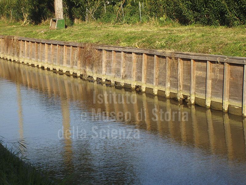 Particolare dell'arginatura del fosso del Molino a Fuoco. Dal 2006, al vecchio sistema in terra battuta, è stata preferita l'arginatura in legno per garantire più efficaci opere di manutenzione e una minore erosione degli argini. Località Molino a Fuoco, Vada.
